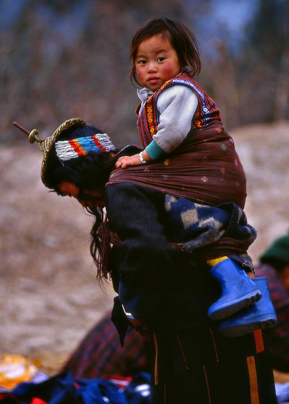 Bhutan child on woman's back